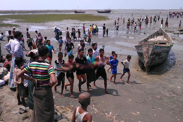 A handout photo taken on April 19 and released to AFP from anonymous Rohingya Muslim minority residents shows people carrying a dead body after a boat capsized off the coast in Sittwe. (AFP photo)