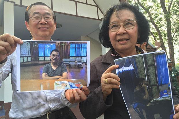 UDD core leader Weng Tojirakarn and his wife, Tida Tawornseth hold photos of Watana Muangsook reportedly taken on Wednesday at a Kanchanaburi military camp. (Photo by Piyarach Chongcharoen)