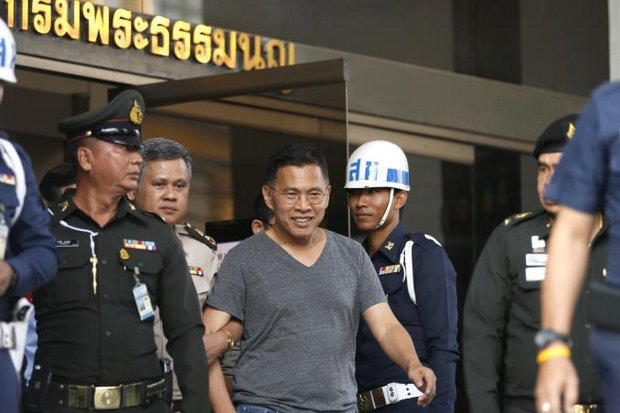 Watana Muangsook is led out of the military court for a bail hearing on Thursday. The Pheu Thai ex-MP was freed on 80,000-baht bail but warned prison could be the next step if he continues