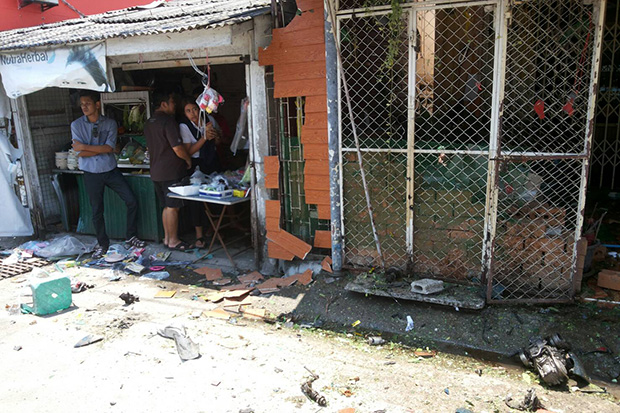 Two people look at damage from a bomb in Soi Lamai Uthis in Muang district in Narathiwat on Monday. Another bomb went off near the Muang police station. (Photo by Waedao Harai)