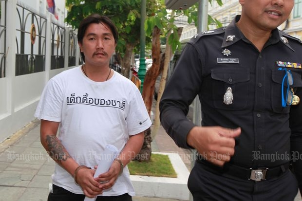 Burin Intin, a member of the anti-coup Resistant Citizen group, is escorted on Saturday to the Bangkok military court which ordered him detained for 12 days. Mr Burin was charged with computer crime and lese majeste. His T-shirt reads