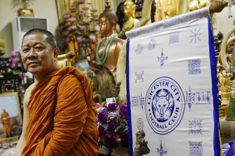 Buddhist monk Phra Prommangkalachan poses for a portrait next to holy cloth with Leicester City's logo while he blesses the team at his temple in Bangkok, Thailand. (Reuters photo)
