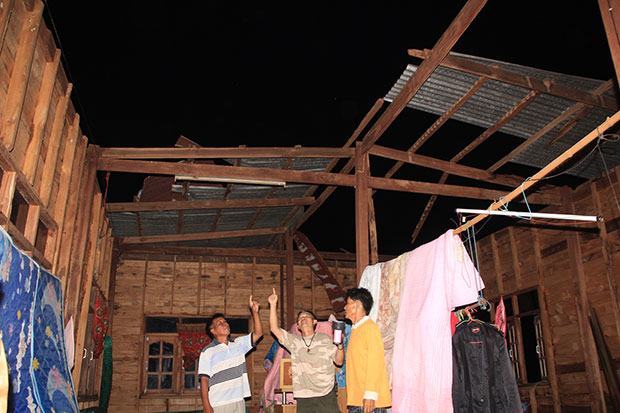 Residents of Nakhon Phanom's Renu Nakhon district point to the missing roof of their house, blown away during a storm on Monday evening. (Photo by Pattanapong Sripiachai)