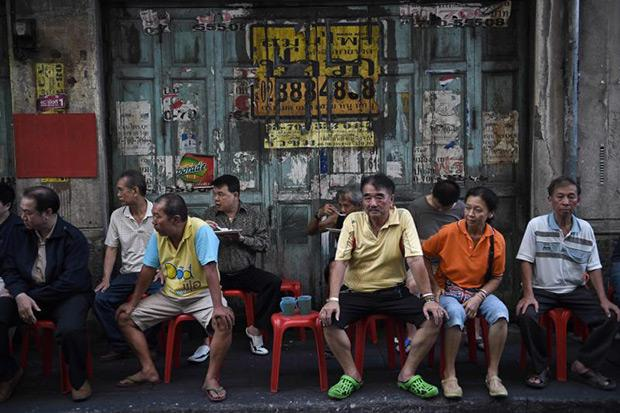 People sit and eat on a sidewalk along a street in Bangkok's Chinatown, one of few city districts yet to be devoured by malls and high-rise condos. But change is coming and fast. A new underground train is now ploughing straight into the heart of the historic quarter. (AFP photo)