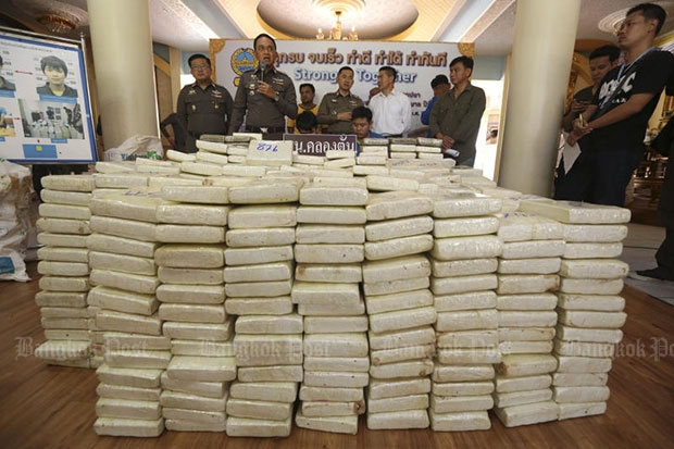 Saharat Khiewpimpa, 20, and Pawan Chankhaikhot, 22, and a pile of compressed marijuana weighing 878kg seized from them are shown at a media briefing on Thursday. (Photo by Patipat Janthong)