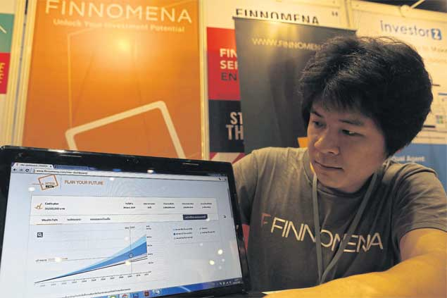 An employee of Finnomena Co shows a website for stock investors at the Startup Thailand 2016, an event held recently by the government to promote startups.PATTARACHAI PREECHAPANICH