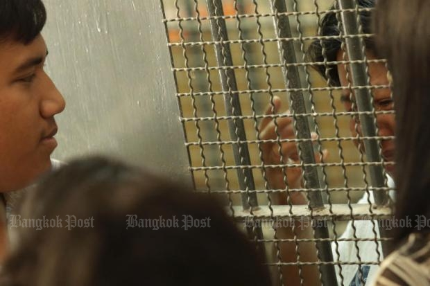 Behind bars: Resistance Citizen group co-leader Sirawith 'Ja New' Seritiwat, left, talks with his mother, Patnaree Charnkij, who is facing lese majeste and computer crime charges.