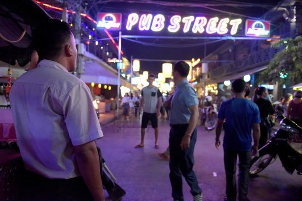 This photo taken Feb 16 shows a Cambodian civilian investigator (left) from Action Pour Les Enfants (APLE) watching tourists walk along a popular bar area in Siem Reap province. (AFP photo)
