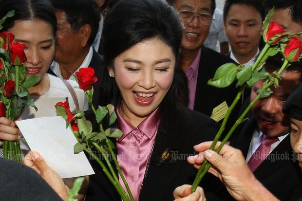 Former prime minister Yingluck Shinawatra greets her supporters upon arriving at the Supreme Court's Criminal Division for Holders of Political Positions to hear witnesses in the rice-pledging programme case on Friday. (Photo by Tawatchai Kemgumnerd)