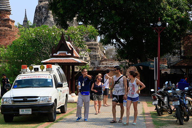 A plainclothes policeman talks to tourists at Ayutthaya Historical Park as safety measures are stepped following the assault and robbery of a German visitor. (Photo by Sunthorn Pongpao)