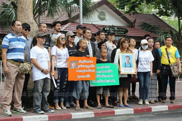 Relatives, friends and witnesses to the killing of Somkiat Sichan, a disabled bread delivery man, hold placards outside the Royal Thai Police Office after they submitted a letter to national police chief Chakthip Chaijinda Monday, asking for justice in the case involving a teen gang with connections. (Photo by Pattanapong Hirunard)