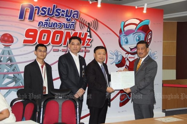 Takorn Tantasith (second right) secretary-general of the National Broadcasting and Telecommunications Commission (NBTC), accepts the application from Suthichai Cheunchoosil, AIS senior vice-president for business relations and development, for AIS to be the lone bidder at next week's restart of the last 4G auction. (Bangkok Post photo)