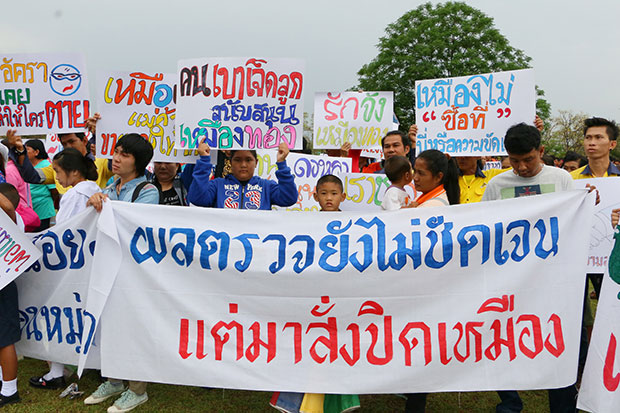 Workers of the gold mining firm Akara Resources Plc and residents living around its mining areas carry banners while they gather at the Phichit provincial hall on Thursday to call on the government to allow the company to stay in business. (Photo by Sitthipoj Kebui)