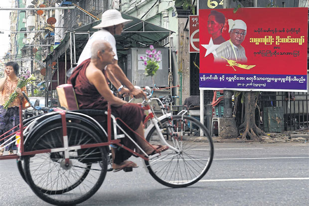A monk riding on a trishaw commutes past a commercial billboard by a local food company with portraits of Myanmar democracy figurehead Aung San Suu Kyi and President Htin Kyaw displayed on a street in Yangon on April 18.AFP