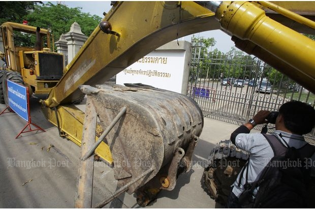 A backhoe blocks one of one of the gates to Wat Dhammakaya, where supporters feared DSI offricers were planning to raid the premises and take away the temple's abbot. (Photo by Apichit Jinakul)