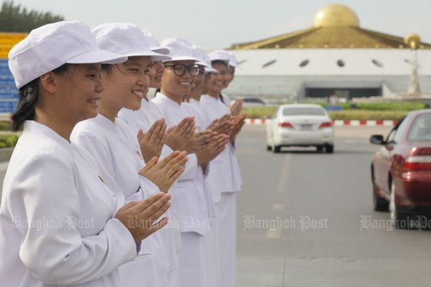Young white-clad devotees greet Buddhists arriving at Wat Dhammakaya in Pathum Thani on Saturday, a Buddhist holy day. The Dek Dee V-Star programme instructs young people in dhamma and holds Buddhist and social activities for them. (Photo by Apichit Jinakul)