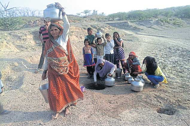 Local residents collect water from a pit dug in the dry bed of a river in Tikamgarh district of Madhya Pradesh.