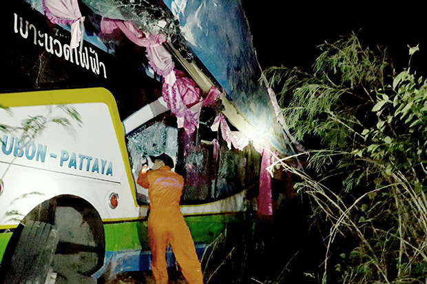 A rescuer examines the wrecked bus that crashed off a curve near kilometre marker 210 on a steep section of Highway 304 in tambon Bupram, Prachin Buri, early Monday morning. (Photo by Manit Sanubboon)