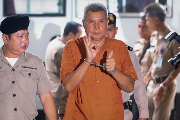 Red shirt-aligned singer and actor Thanat Thanawatcharanont (centre) is escorted by police officers as he arrives at the Criminal Court on a charge of lese majeste in Bangkok June 1. (EPA photo)