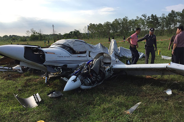 Officials examine the wreckage of the twin-engined, four-seater DA42 trainer in the field where it crashed immediately after taking off from Nakhon Phanom airport early Thursday morning, killing all three people on  board. (Photo by Pattanapong Sripiachai)
