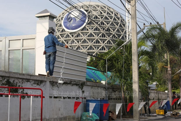 A worker installs metal sheets in place of barbed wire on the fence of Wat Phra Dhammakaya on Thursday as the abbot continues to refuse to acknowledge money-laundering charges. (Photo by Pattanapong Hirunard)