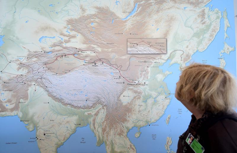 A woman walks past a map of China and Central Asia with red line signifying the ancient trade route known as the Silk Road at the