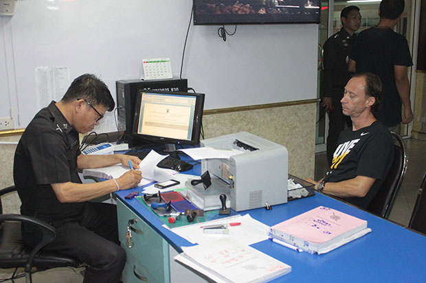 Luga Viggiani, an Italian national, right, lodges a complaint with a police officer at Pattaya police station in Chon Buri province early Wednesday, accusing a British friend of  drugging and robbing him of 600,000 baht cash before dumping him at Pattaya beach in Chon Buri. (Photo by Chaiyot Puttanapong)