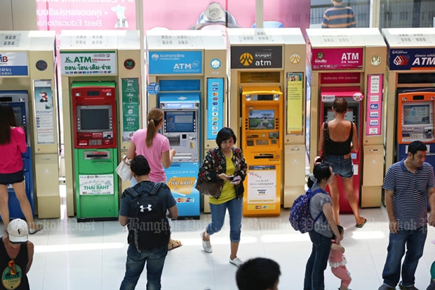 People withdraw their money from ATM machines installed at a department store in Bangkok in May 2016. (Bangkok Post file photo)