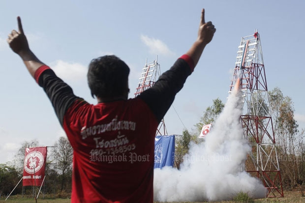 A competitor cheers after his rocket takes off from its launch pad during the annual bang fai festival in Yasothon on May 10, 2015. (Photo by Pattarapong Chatpattarasill)