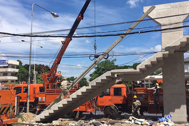 Metropolitan Electricity Authority workers on Monday remove the annoying pole that partially blocked the stairway, built around it, on this new pedestrian overpass in Muang district of  Nonthaburi. (Metropolitan Electricity Authority photo)