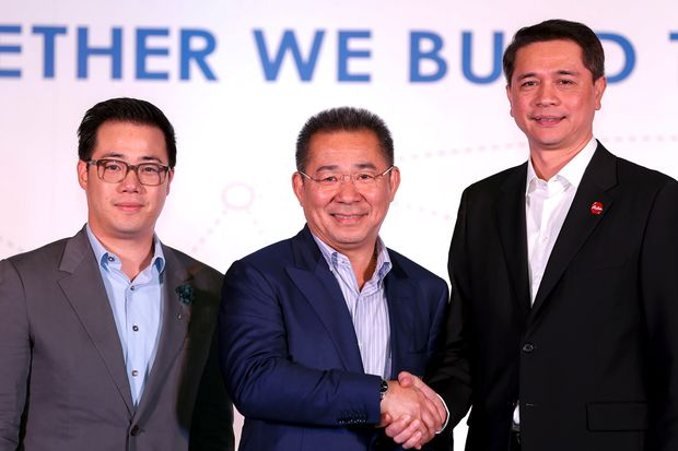 From left: King Power CEO Aiyawatt Srivaddhanaprabha, King Power chairman and billionaire Vichai Srivaddhanaprabha and Thai AirAsia CEO Tassapon Bijleveld, pose for photographs after a news conference at the King Power headquarters in Bangkok on Tuesday. (Reuters photo)