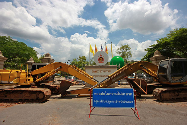 Two large backhoes block the main entrance of Wat Dhammakaya in Khlong Luang district in Pathum Thani on Wednesday. (Photo by Pongpat Wongyala)