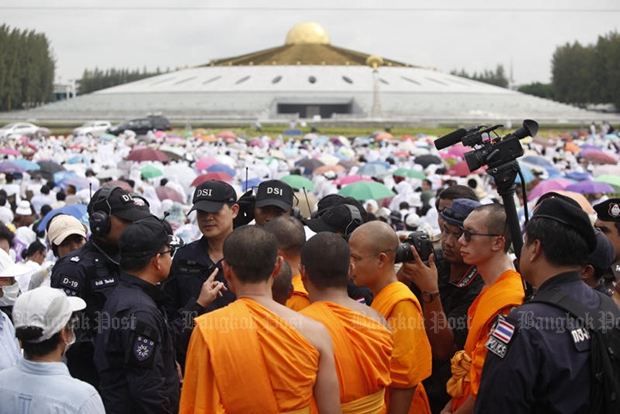 Officials from the Department of Special Investigation are seen talking with monks inside the grounds of Wat Phra Dhammakaya in Pathum Thani on Thursday morning. (Photo by Pattarapong Chatpattarasill)