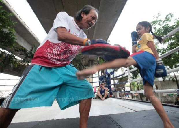 A boxing trainer instructs a 7-year-old girl in Muay Thai boxing. Some experts fear children are at risk of brain damage if they are hit too hard in the ring.File photo