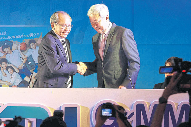 CTH chairman Wichai Thongtang (left) greets GMM Grammy chairman Paiboon Damrongchaitham at a media event in July 2014. CTH, the pay TV operator that won the broadcast rights to English Premier League football, is expected to shut down soon.SOMCHAI POOMLARD