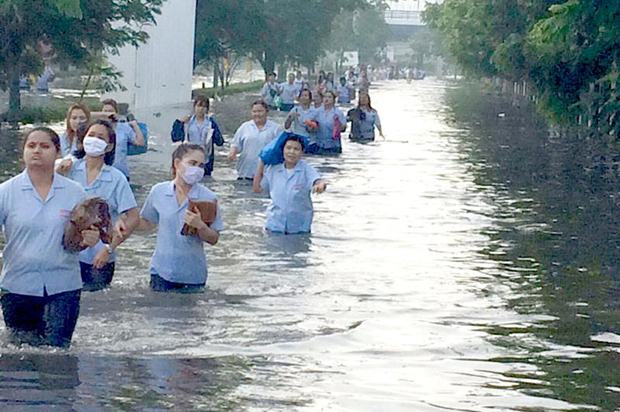 Employees wade through flood water at Bang Poo Industrial Estate on Wednesday. (Photo by Sutthiwit Chayutworakan)
