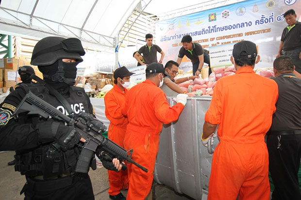 Armed police watch as anti-narcotics officials handle tonnes of methamphetamine pills in bins, readying the drugs for incineration, at Bang Pa-in Industrial Estate in Bang Pa-in district, Ayutthaya, on Friday. (Photo by Sunthorn Pongpao)