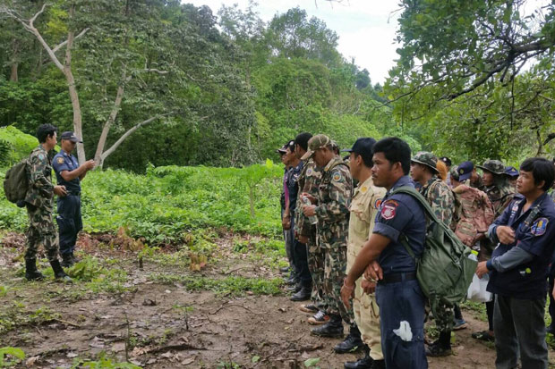 Military and police officers and district officials are joined by village volunteers to look for an air force helicopter missing since Saturday between Chanthaburi and Rayong provinces.
