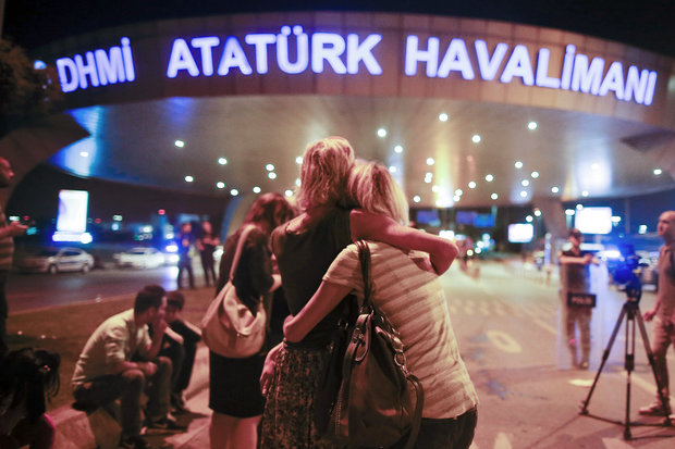 Passengers embrace each other as they wait outside Istanbul's Ataturk airport, early on Wednesday following their evacuation.  (Photo by AP)