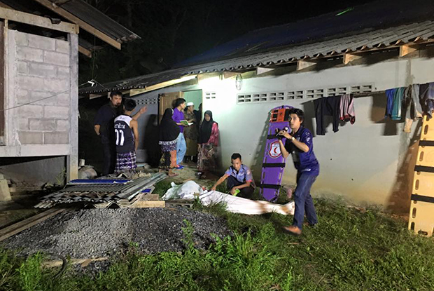 Officials examine the scene at a house in tambon Lidon of Pattani's Muang district after a gun attack on Tuesday night where two men were killed and another wounded. (Photo by Maluding Tido)
