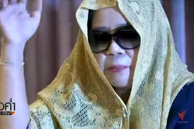 Montra Yokrattanakan, also known as Ying Kai and several other names, appeared in front of the media in a semi-disguise to defend herself against charges she is running a confidence game. (Video grab from ThaiPBS)