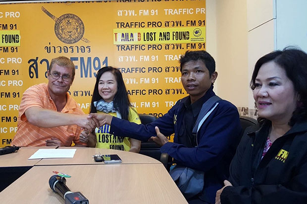 Yutthana Mainoi (second from right), 36, a motorcycle taxi driver, shakes hands with Daniel Kofmel (left), 45, a Swiss national, after returning a wallet containing 10,000 Swiss francs (360,000 baht) to him at the FM91 traffic radio station in Bangkok on Friday. (Post Today photo)
