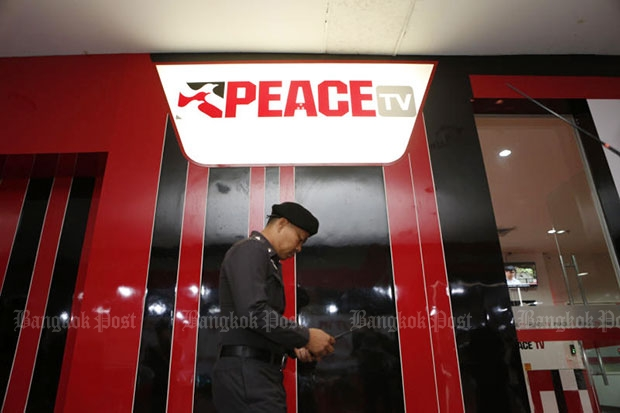 A policeman walks outside the office of Peace TV at Imperial Lat Phrao department store in this June 19, 2016 file photo. The NBTC on Monday ordered the station closed for 30 days, prompting immediate and strong resistance from the red-shirt leaders. (Photo by Pattarapong Chatpattarasill)
