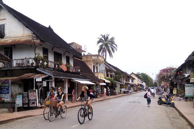 Tourists pedal through the old Lao capital of Luang Prabang. Thailand proposed stronger tourism links with Laos at talks between the Thai and Lao prime ministers on Wednesday. (Photo by Pongpet Mekloy)