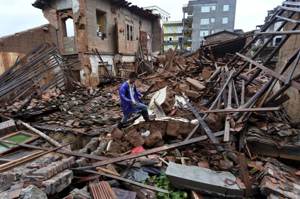 In this July 9, 2016 photo, a villager walks around a destroyed house, after torrential rainfall brought by typhoon Nepartak, in Lingcuo village of Xindu Township in Putian, southeast China's Fujian Province. Typhoon Nepartak weakened to a strong tropical storm Saturday as it lashed China's east coast, bringing powerful winds and heavy rains that toppled houses and inundated roads. (Zhang Guojun/Xinhua News Agency via AP)