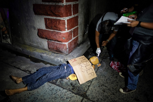 Police officers examine the body of a man, his face wrapped with packing tape and a placard reading