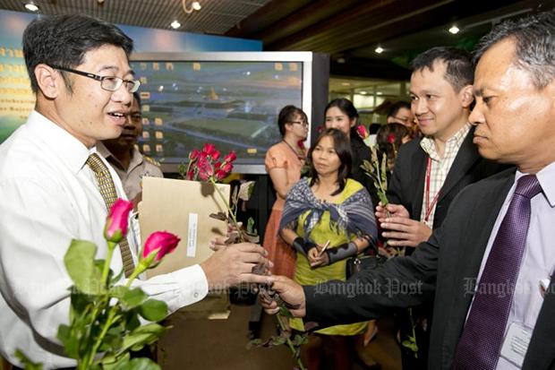 Somchart Thammasiri (left), sacked legal adviser to the Parliament Secretariate, receives roses from secretariate staff on Monday morning. (Photo by Krit Promsaka na Sakolnakorn)