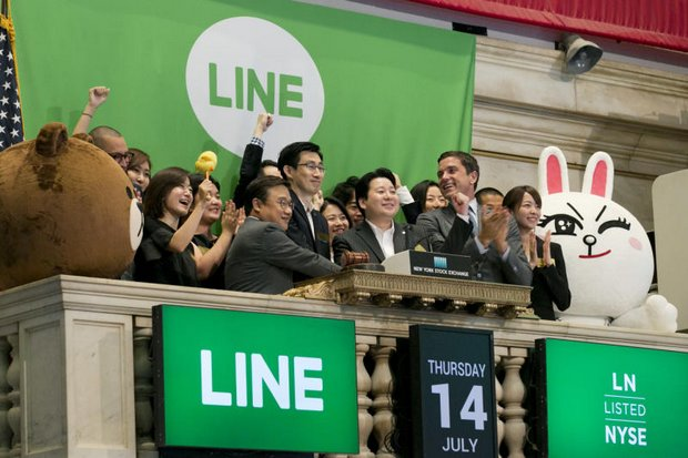 Executives of messaging app Line ring the opening bell for their company's IPO at the New York Stock Exchange, as initial shares surged by a third in early trading. (AP photos)