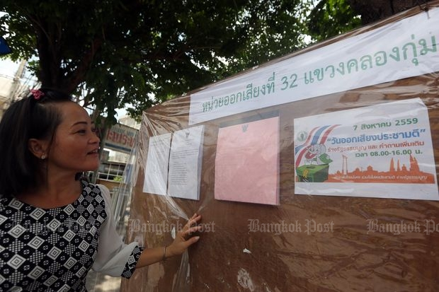 A woman checks names of eligible voters for the Aug 7 referendum put up by the Bung Kum district in Bangkok on Tuesday. (Photo by Weerawong Wongpreedee)