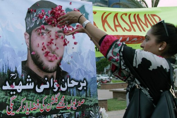 A Pakistani in Lahore showers rose petals on a picture of slain Kashmiri leader Burhan Wani as the country observes its annual 'black day' of solidarity with disputed Kashmir. The poster reads, 'You will always be remembered'. (AP photo)